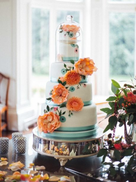 Painted peach and teal wedding cake